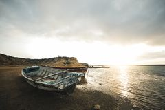 Beached boat and the sunrise. A beached boat lights up with the shines of the sunrise in Punta Gallinas, Guajira, Colombia royalty free stock image