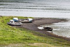 Beached boats. Along the rocky shore in Gesto Bay in Struan in the Isle of Skye, Scotland royalty free stock photos