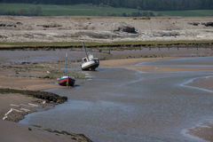 Beached boats. A seascape of a harbor harbour at low tide with two small boats beached in the estuary royalty free stock images