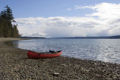 Beached Canoe. Canoe grounded on the shores of Burfoot Park with the waters of Budd Inlet (South end of the Puget Sound) leading to the Capital City of Olympia royalty free stock images