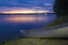 Beached Canoe at dusk. Long exposure image of canoe beached along north woods forest lake at sunset royalty free stock image