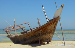Beached dhow at Wakrah. A beached dhow at Wakrah, south of Doha, Qatar. The vessel seems to have been abandoned long ago and is little more than a wreck now stock image