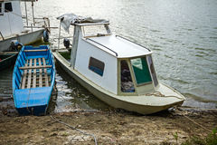 Beached fisherman boat, tied to a tree. Royalty Free Stock Photos