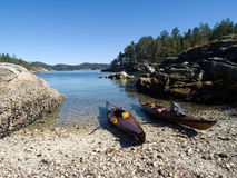 Beached Kayaks on narrow inlet. While kayaking in the Breton Islands off Vancouver Island, British Columbia we took a lunch stop on a small shell-encrusted Royalty Free Stock Images