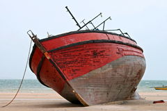 Beached. An old red boat beached. front view, indian ocean in the background royalty free stock photo