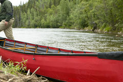 Beached, red inflatable canoe on river in Alaska Stock Photos