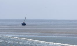 Beached sailing boat. At the dutch coast royalty free stock photos