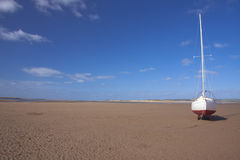 Beached yacht. Yacht or boat at anchor on beach waiting for high tide Stock Photos