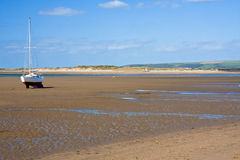 Beached yacht. Yacht or boat on beach waiting for high tide along devon coast Royalty Free Stock Photo