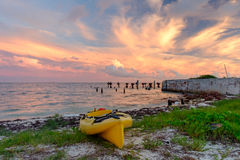 A beached yellow sea kayak on the beach at Fort Jefferson at sun Stock Photos