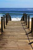 Beaches. Wooden bridge leading to the sandy shore Royalty Free Stock Images