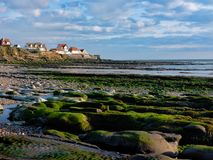 The town of Audreselles at low tide. The beaches around the town of Audresseles are wide, with rocks and tidal pools inbetween. At late afternoon the houses of royalty free stock photo
