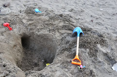 On the beaches of tunnel engineering. The children play on the beach to dig tunnels and plastic tools everywhere Royalty Free Stock Photo