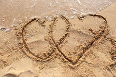 Beaches waves and heart shape drawn. Royalty Free Stock Photography