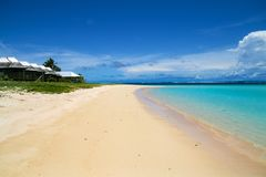 Beachfront fale cottages on tropical white sand beach and shallo stock photo