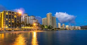Beachfront hotell på Waikiki sätter på land i Hawaii på natten Royaltyfria Bilder