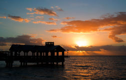 Beachfront II. Color photo of hut on ocean with sunset, waves, and clouds stock image