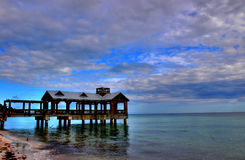 Beachfront III. Color photo of hut on ocean with sunset, waves, and clouds royalty free stock photo