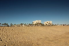 Beachfront Real Estate. Venice beach buildings, palm trees, and sand royalty free stock photo