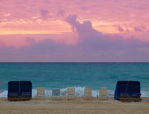 Beachfront at sunset. Chairs at the beach overlooking sunset Stock Photography