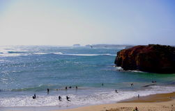 Beachgoers at the Great Ocean Road. Photograph taken at the Bay of Martyrs featuring dramatic coastline and people playing in the surf (Great Ocean Road stock photo
