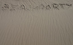 Beachparty. The word beachparty written into the sand on the beach in one line Royalty Free Stock Image