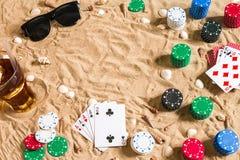 Beachpoker Chip e carte sulla sabbia Intorno alle conchiglie, agli occhiali da sole ed alla bevanda fredda in un vetro Vista supe Immagini Stock Libere da Diritti