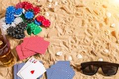 Beachpoker Chip e carte sulla sabbia Intorno alle conchiglie, agli occhiali da sole ed alla bevanda fredda in un vetro Vista supe Fotografia Stock Libera da Diritti