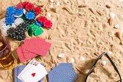 Beachpoker Chip e carte sulla sabbia Intorno alle conchiglie, agli occhiali da sole ed alla bevanda fredda in un vetro Vista supe Fotografia Stock