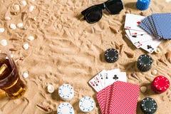 Beachpoker Chip e carte sulla sabbia Intorno alle conchiglie, agli occhiali da sole ed alla bevanda fredda in un vetro Vista supe Immagine Stock