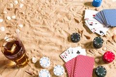 Beachpoker Chip e carte sulla sabbia Intorno alle conchiglie ed alla bevanda fredda in un vetro Vista superiore Immagini Stock Libere da Diritti