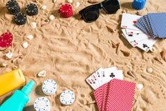 Beachpoker Microprocesadores y tarjetas en la arena Alrededor de las conchas marinas, gafas de sol y crema del bronceado Visión s Fotos de archivo libres de regalías