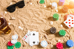 Beachpoker Puces et cartes sur le sable Autour des coquillages, des lunettes de soleil et de la boisson froide dans un verre Vue  Image libre de droits
