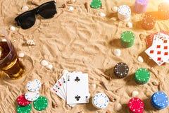 Beachpoker Spaanders en kaarten op het zand Rond de zeeschelpen, de zonnebril en de koude drank in een glas Hoogste mening royalty-vrije stock afbeelding