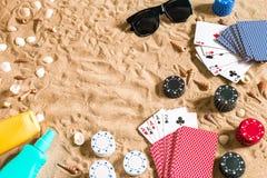 Beachpoker Spaanders en kaarten op het zand Rond de zeeschelpen, zonnebril en bruine kleurroom Hoogste mening royalty-vrije stock afbeeldingen