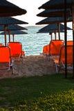 Beachscape con las sillas anaranjadas, las sombrillas cubiertas con paja y la isla en un fondo fotografía de archivo