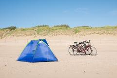 Beachshelter och cyklar på stranden Arkivbild