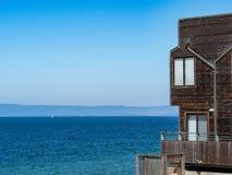 Το σύγχρονο ξύλινο σπίτι beachside αγνοεί το τροπικά νερό και sailboat στοκ φωτογραφία