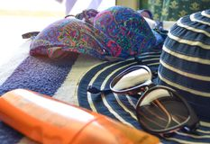 Beachware y accesorios en el fondo azul-blanco de la toalla foto de archivo
