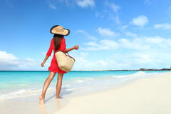 Beachwear woman walking with sun hat and beach bag. Beachwear woman tourist with straw sun hat and beach bag walking on tropical summer vacation wearing sunhat Royalty Free Stock Images