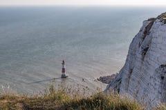 Beachy Head kritaklippa med fyren och skugga och långa gras Arkivbild