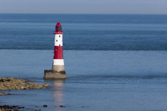 Beachy Head Lighthouse and calm seas. Red and white lighthouse on still, blue waters situated at the bottom of white, chalk cliffs Royalty Free Stock Photography