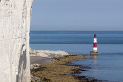 Beachy Head Lighthouse and calm seas. Red and white lighthouse on still, blue waters situated at the bottom of white, chalk cliffs Royalty Free Stock Photos