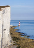 Beachy Head Lighthouse and calm seas. Red and white lighthouse on still, blue waters situated at the bottom of white, chalk cliffs Stock Images