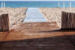 Beack. Wooden walkway on the white sand Royalty Free Stock Photos