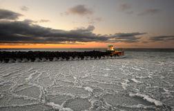 Beacon. Lighthouse at the harbor inlet on a winter evening with ice in water Stock Image