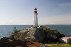 The Beacon. A lighthouse sits atop a massive rock, overlooking the Pacific Ocean Stock Photography