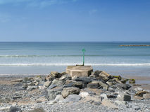 Beacon and beach in Wales UK. Green beacon and rocky beach in Borth Wales UK Stock Images