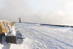 Beacon and bench on snowy mole Stock Photos