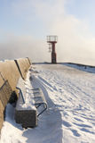 Beacon and bench on snowy mole Royalty Free Stock Photography